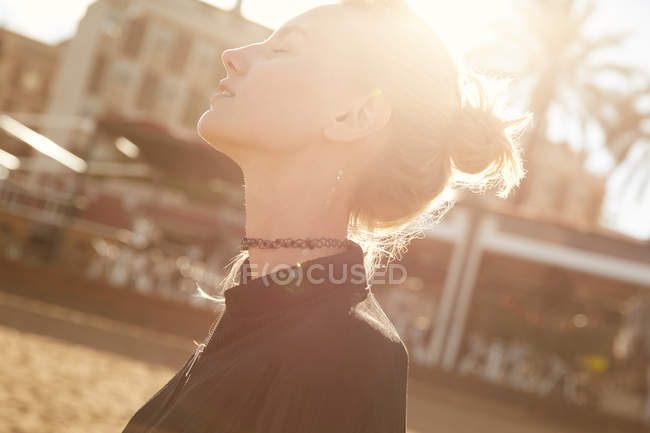 Side view of attractive woman with closed eyes standing on street at sunny day — Stock Photo