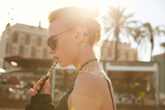 Side view of woman in sunglasses smoking electronic cigarette on street in barcelona — Stock Photo