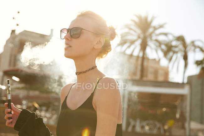 Portrait of young woman in sunglasses smoking electronic cigarette on street in barcelona — Stock Photo