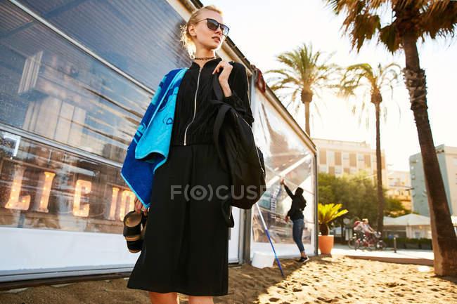 Vue à angle bas de belle femme en lunettes de soleil marchant avec serviette sur la plage publique à Barcelone — Photo de stock