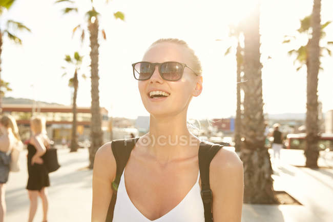 Happy woman in sunglasses standing on street in barcelona — Stock Photo