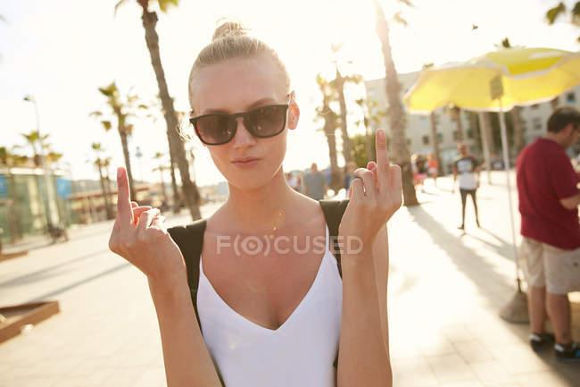 Jovem mulher em óculos de sol mostrando os dedos médios no mercado de rua em barcelona — Fotografia de Stock