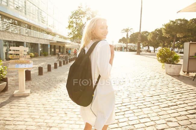 Femme souriante marchant avec sac dans la rue à Barcelone — Photo de stock