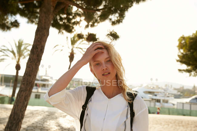 Attractive woman standing on quay in barcelona and touching hair — Stock Photo