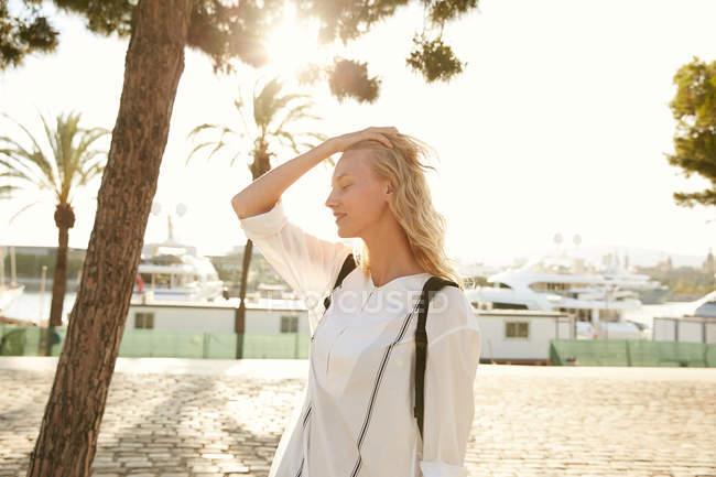 Vista lateral da mulher atraente em pé no cais em barcelona — Fotografia de Stock
