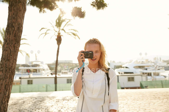 Smiling young woman taking photo with digital camera on street in barcelona — Stock Photo