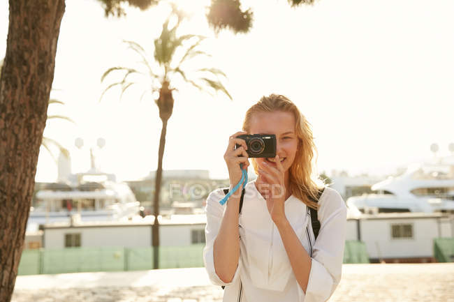 Smiling young traveler taking photo with digital camera on street in barcelona — Stock Photo