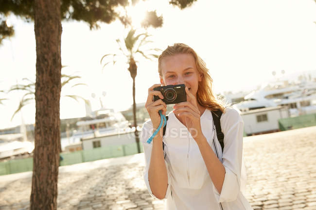 Smiling young tourist taking photo with digital camera on street in barcelona — Stock Photo