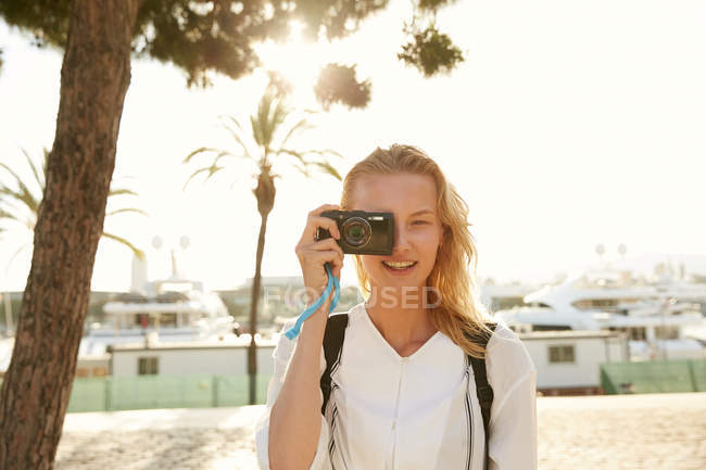 Cheerful young tourist taking photo with digital camera on street in barcelona — Stock Photo