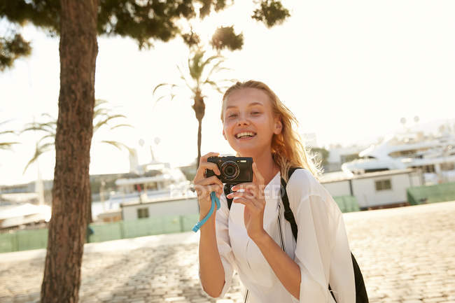 Happy young tourist taking photo with digital camera on street in barcelona — Stock Photo