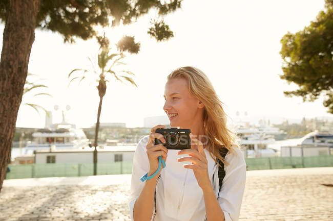 Smiling young traveler walking with camera on street in barcelona — Stock Photo