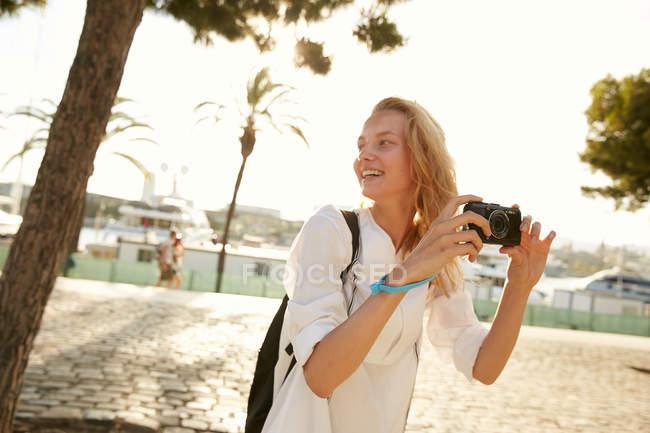 Jeune touriste souriant marchant avec caméra dans la rue à Barcelone — Photo de stock