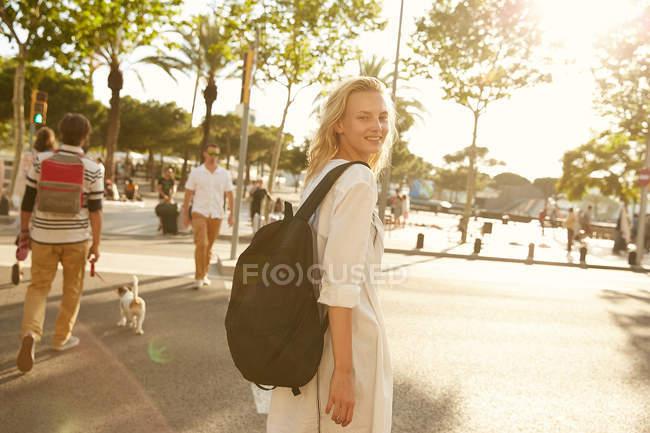 Glückliche Frau, die mit Tasche auf der Straße spaziert und in Barcelona in die Kamera schaut — Stockfoto