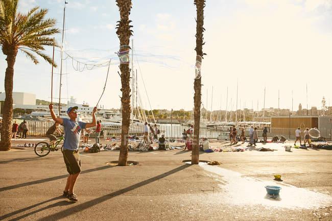 SPAIN, BARCELONA - 20 JUNE 2016: man making soap bubble on embankment — Stock Photo