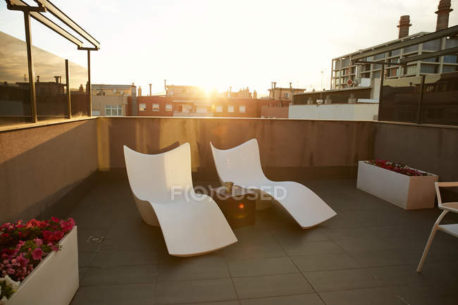 Two sun loungers and table on terrace during sunset in city — Stock Photo