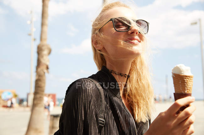 Smiling attractive blonde tourist in sunglasses eating ice cream on street — Stock Photo