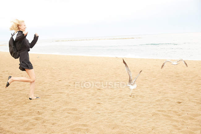 Side view of happy woman in black dress and bag running after seagulls on sandy sea beach — Stock Photo