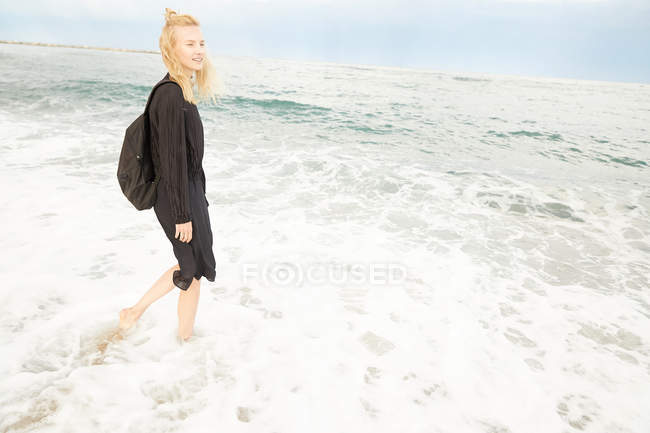 Beautiful smiling woman in black dress and bag standing in sea — Stock Photo