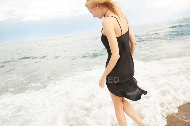 Beautiful smiling woman in black dress standing in sea and looking at water — Stock Photo
