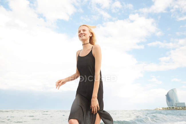 Low angle view of happy beautiful woman in black dress walking on sea beach — Stock Photo