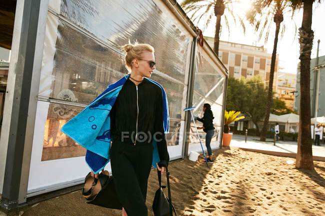 Belle femme en lunettes de soleil marchant avec serviette sur la plage publique à Barcelone — Photo de stock
