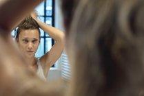 Woman styling hair in bathroom mirror — Stock Photo