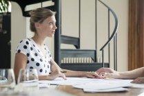 Кавказская женщина, работающая с коллегой — стоковое фото