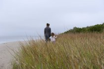 Мать и дочь гуляют по пляжу в облачный день — стоковое фото
