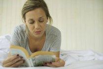 Женщина лежит на желудке, читая книгу — стоковое фото