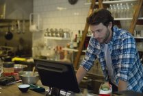 Cafe owner looking at cash register — Stock Photo