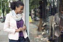 Afro-americana mulher olhando para loja janela — Fotografia de Stock