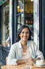 Smiling Woman sitting at sidewalk cafe — Stock Photo