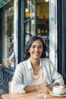 Smiling Woman sitting at sidewalk cafe — Stock Photo