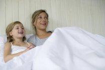 Mutter und Tochter vor dem Fernseher zusammen im Bett — Stockfoto