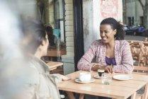 Female Friends talking at sidewalk cafe — Stock Photo