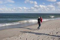 Vacanziere che cammina sulla spiaggia con bambino piccolo sul retro durante la bassa stagione — Foto stock