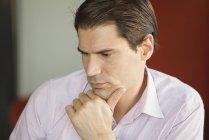 Porträt eines Geschäftsmannes, der die Hand am Kinn hält und tief in Gedanken sitzt — Stockfoto