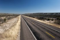 Estrada vazia através da paisagem do deserto — Fotografia de Stock