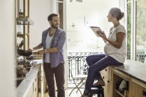 Wife looking on as husband preparing meal at home kitchen — Stock Photo