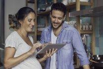 Пара с помощью цифрового планшета вместе дома — стоковое фото