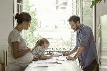 Parents en regardant la fille dessin avec pointes feutres — Photo de stock