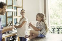 Girl chatting with parents preparing family meal in kitchen — Stock Photo