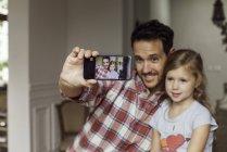 Padre e figlia che propongono per selfie — Foto stock
