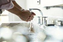 Обрезанное фото человека, моющего руки в раковине ванной комнаты — стоковое фото