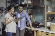 Couple in kitchen looking at digital tablet together — Stock Photo