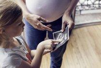 Mãe usando ultra-som foto para preparar a filha para chegada iminente de novo irmão — Fotografia de Stock