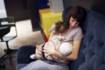 Mother nursing infant sitting on the couch — Stock Photo