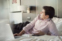 Businessman lying on hotel bed with cell phone and laptop computer, looking away in thought — Stock Photo