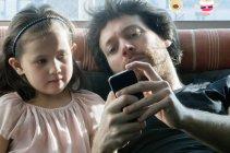 Père et jeune fille regardant smartphone ensemble — Photo de stock