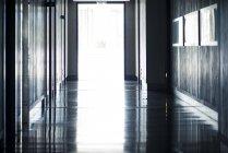 Open doors at end of empty hallway — Stock Photo